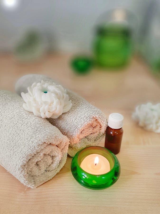 Badekurortaromatherapiekonzept Tuch, ätherisches Öl, handgemachte Blumenseife, brennende Kerze im grünen Glas auf Holztisch lizenzfreies stockfoto