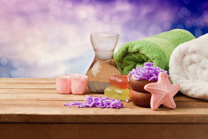 Badekurorteinstellung mit Seife und Tüchern auf Holztisch über bokeh Hintergrund lizenzfreie stockfotografie