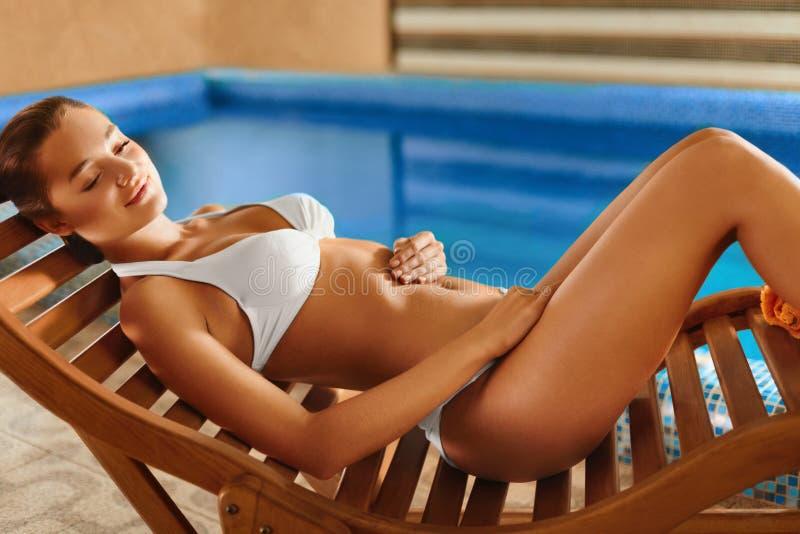 Badekurortkörperpflege Mädchen, das im Klappstuhl sich entspannt lizenzfreie stockfotografie