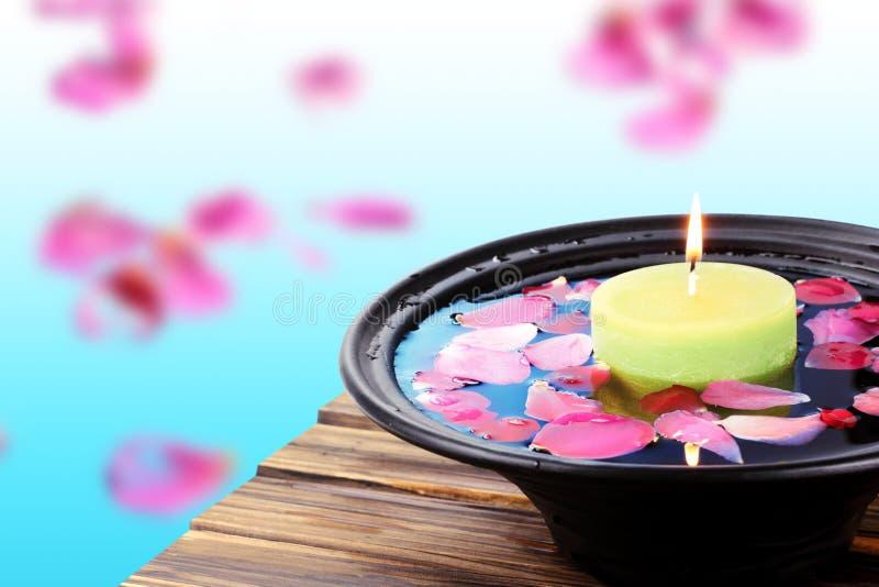 Badekurortkerze und rosafarbene Blumenblätter lizenzfreie stockfotografie