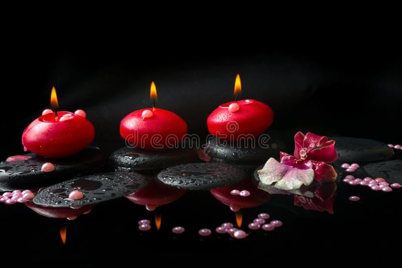 Badekurortkonzept der weißen und roten Orchidee (cambria), drei rote Kerzen stockfotos