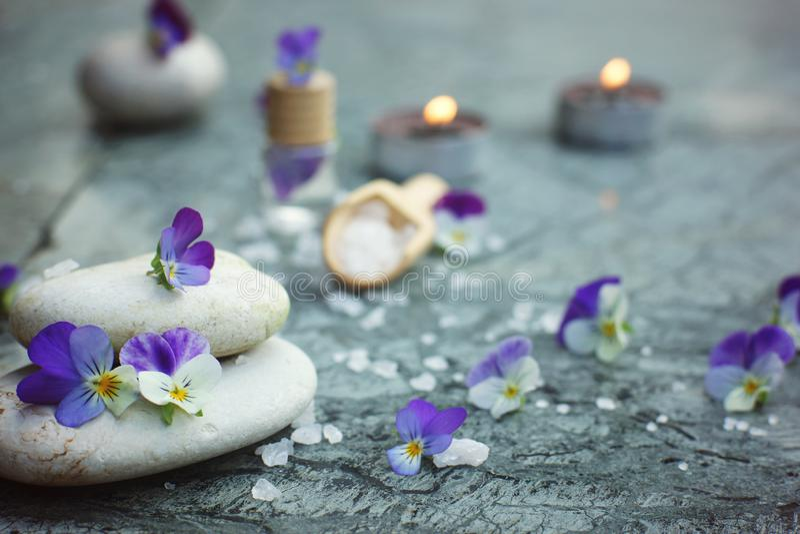Badekurortkonzept mit brennenden Kerzen, Massagesteinen und Seebadesalze, Dekoration von purpurroten Blumen stockfotos
