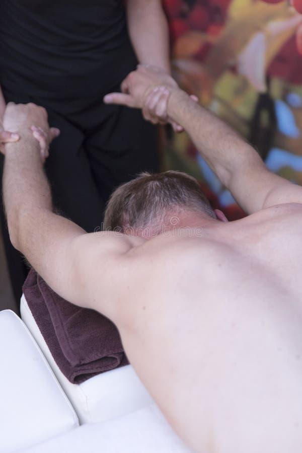 Badekurortmann Frau, die entspannende Rückenmassage in der Cosmetology-Badekurort-Mitte genießt Körperpflege, Hautpflege, Wellnes lizenzfreies stockbild