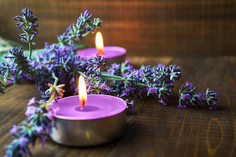 Badekurortmassageeinstellung mit Lavendelblumen, duftende Aromakerzen auf hölzernem Hintergrund stockfotografie