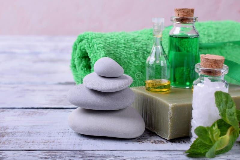 Badekurortsatz: Massagesteine, aromatisches ?l, Seesalz, gr?nes Gel, organische Seife und gr?nes Tuch stockfotografie