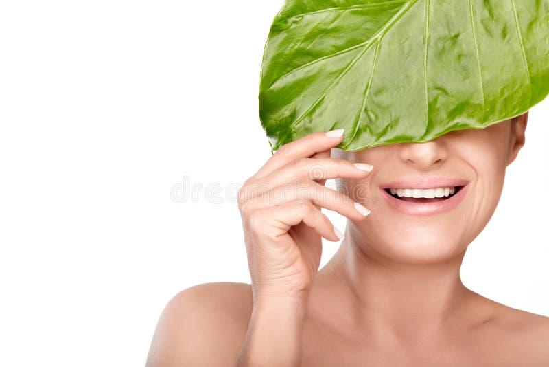 Badekurortschönheitsporträt einer lachenden Frau, die hinter einem frischen grünen Blatt sich versteckt stockfoto