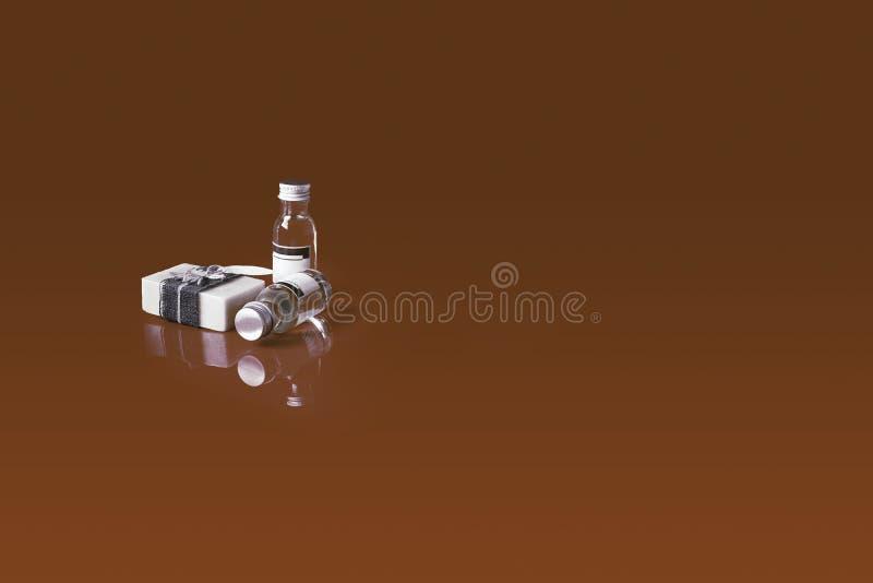 Badekurortseife, wesentliches Aromaöl, Badekurort theaphy Konzeptprodukte auf dem braunen Reflexionshintergrund lizenzfreie stockfotos
