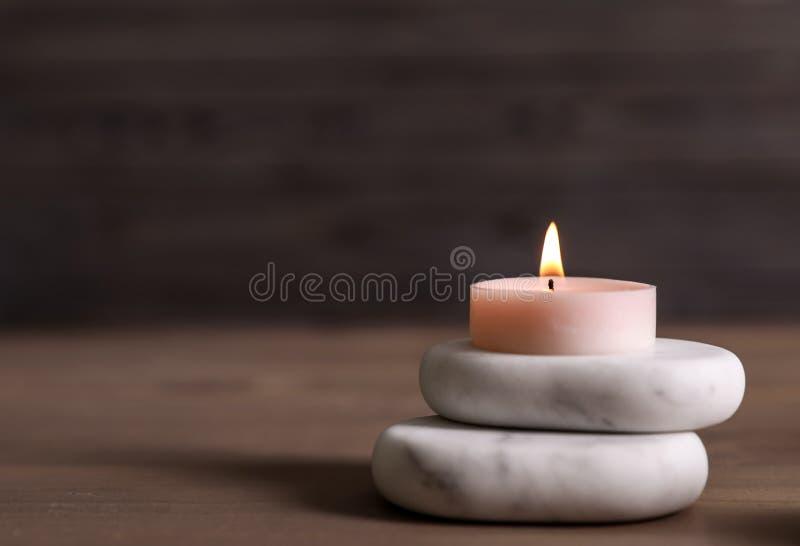 Badekurortsteine und brennende Kerze auf Holztisch lizenzfreie stockbilder