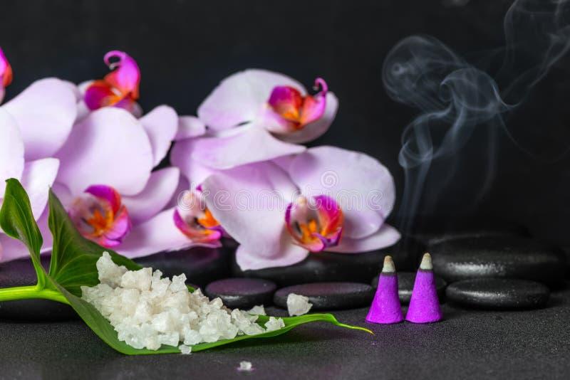 Badekurortstillleben des Seesalzes auf Blatt, lila Orchidee mit Tropfen und brennenden Aromaweihrauchkegeln über schwarzen Zenste lizenzfreies stockbild