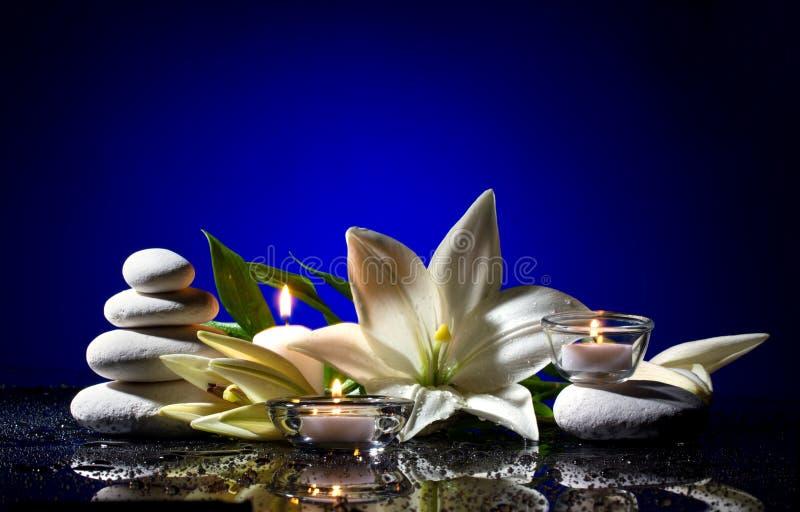 Badekurortstillleben mit Blume, Steinen und Kerzen stockbilder