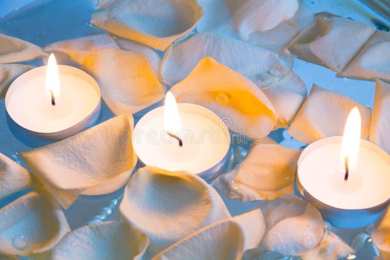Badekurortstillleben mit Kerze und den rosafarbenen Blumenblättern über hellem Hintergrund lizenzfreie stockfotografie