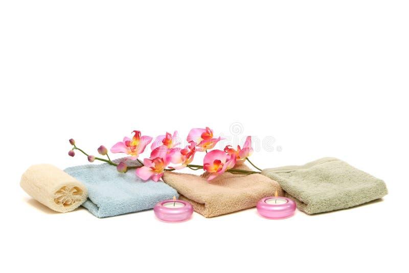 Badekurorttücher, Kerzen, Luffa und rosafarbene Orchidee stockfotografie
