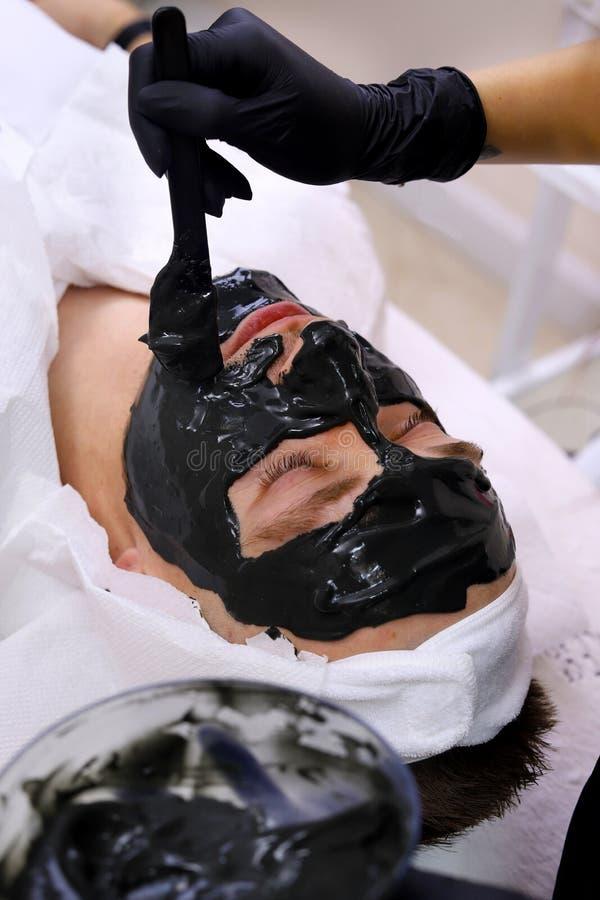 Badekurorttherapie für die Männer, die schwarze im Gesichtmaske empfangen lizenzfreie stockbilder