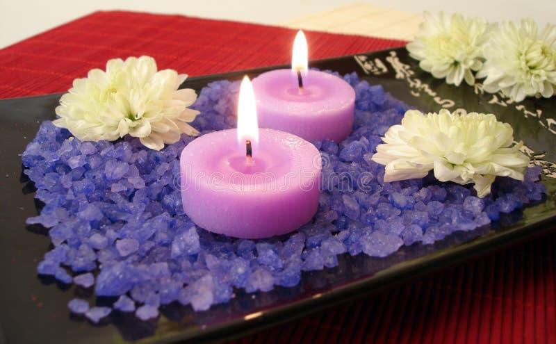Badekurortwesensmerkmale (violettes Salz, Kerzen und Blumen) stockbilder