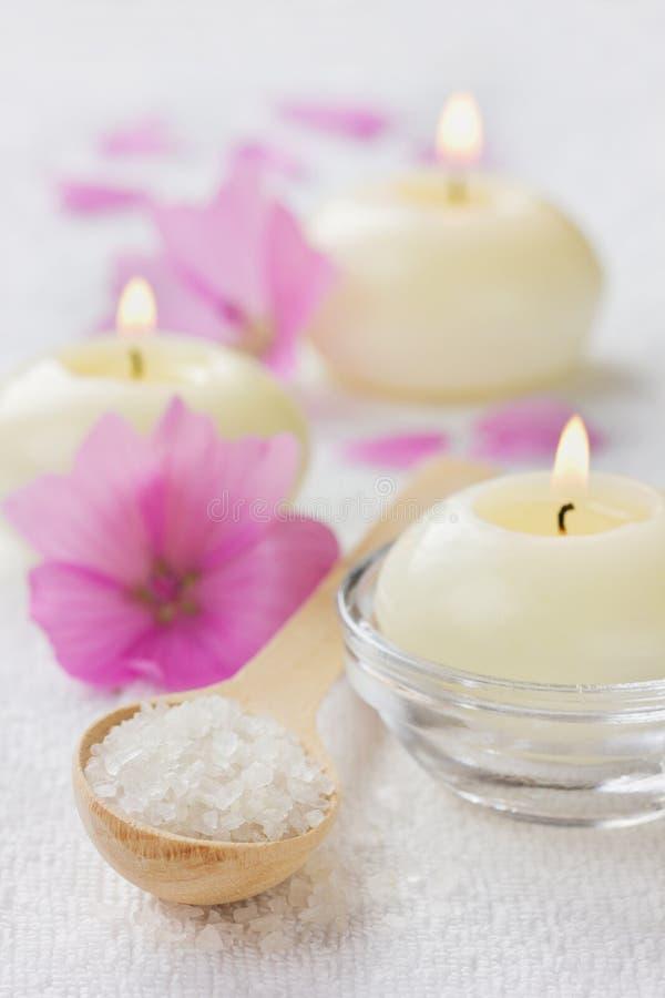 Badekurortzusammensetzung mit Seesalzbad im hölzernen Löffel, in den rosa Blumen und in brennenden Kerzen auf einer weißen Oberfl stockfoto