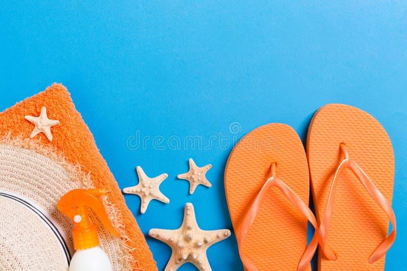 Bademantel Sonnenschutzcreme, Strohhut, Flip Flops, Handtuch und Muscheln auf farbigem Hintergrund stockfotos