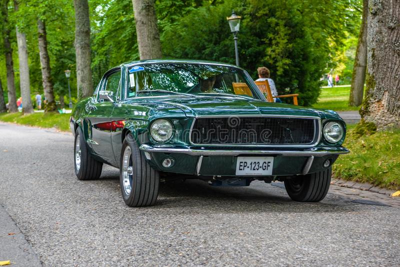 BADEN BADEN, GERMANY - JULY 2019: dark green FORD MUSTANG coupe first generation 1964 1973, oldtimer meeting in Kurpark royalty free stock images