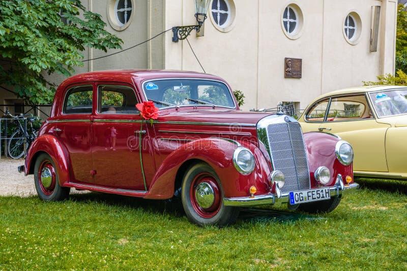 BADEN BADEN, GERMANY - JULY 2019: dark red MERCEDES-BENZ 220 limousine sedan W187, oldtimer meeting in Kurpark stock image