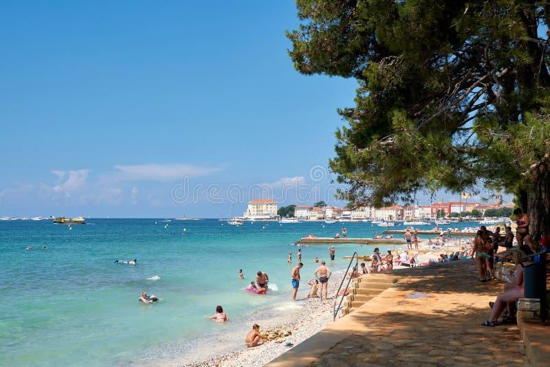 Badende toeristen op het strand van Porec in Kroatië stock afbeeldingen