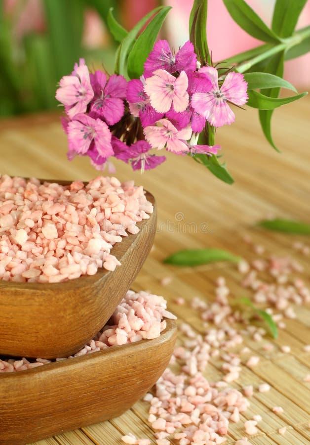 Badesalz in der hölzernen Schüssel und in den rosafarbenen Blumen. lizenzfreie stockfotos