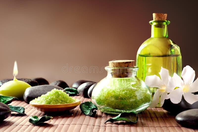 Badesalz und Öl mit Blumen und Steinen brünieren Hintergrund lizenzfreie stockbilder