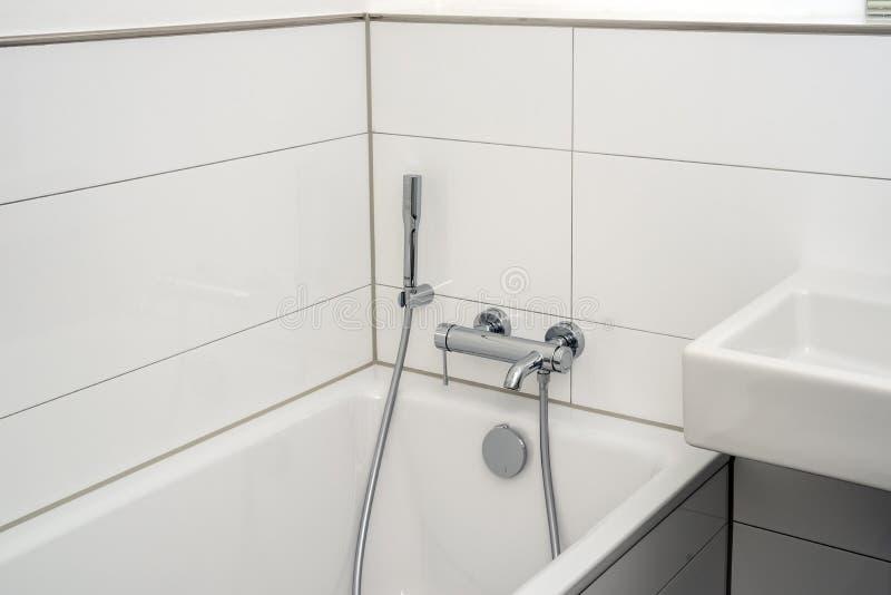 Badewanne mit Installationen im modernen weißen Luxusbadezimmer stockfoto