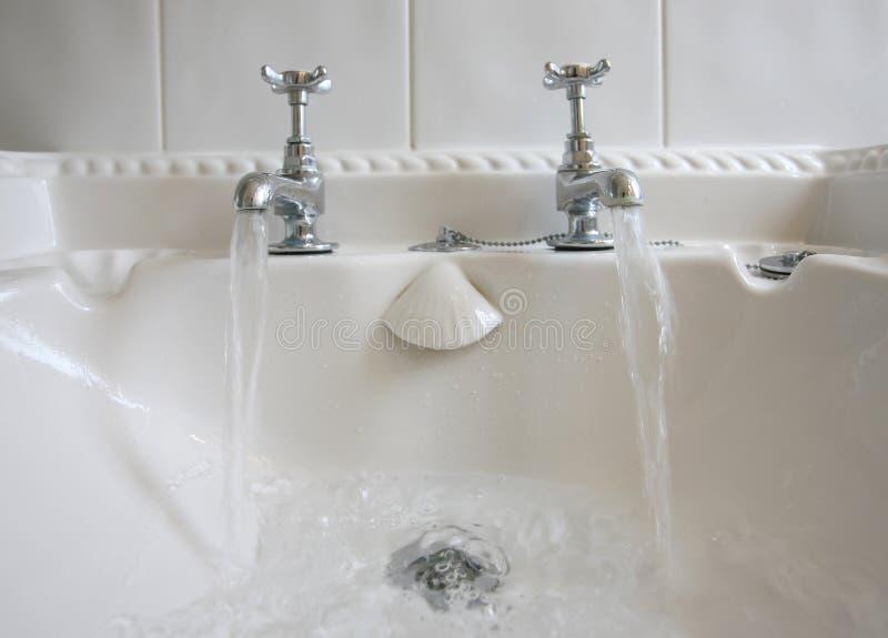 Badezimmer-Hähne und fließendes Wasser stockfoto