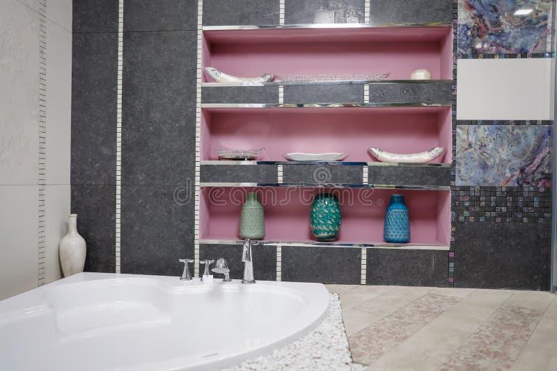Badezimmer mit Badewanne in der Ecke und drei rosa Regalen in der Rückseite Auf den Wänden sind dekoratives, mehrfarbiges Mosaik stockbilder