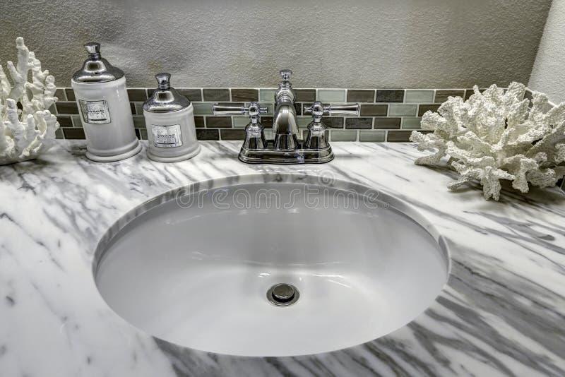 Badezimmereitelkeitskabinett mit weißer Granitspitze Wanne und decorat stockfotografie