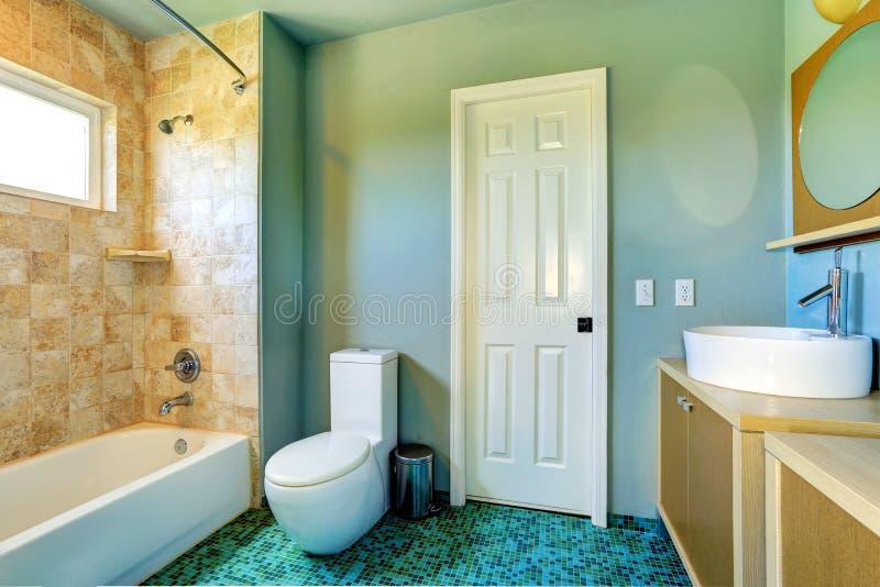 Badezimmerinnenraum in hellblauem mit Fliesenwandordnung lizenzfreies stockbild