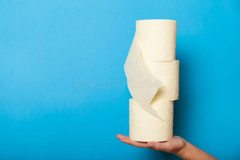 BadezimmerToilettenpapierrolle in der Hand, gesundheitliches Konzept des Hygienegewebes lizenzfreie stockfotos