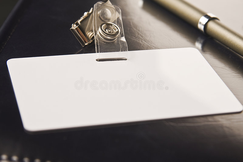 Badge. White badge lays on organizer with a black cover stock photos