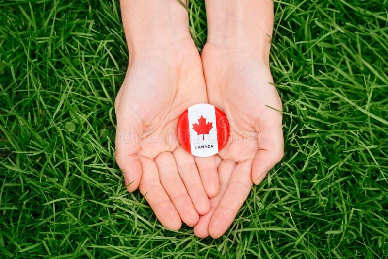 badge con la foglia di acero canadese bianca rossa della bandiera che si trova nell'erba sul fondo verde della natura della fores immagini stock libere da diritti
