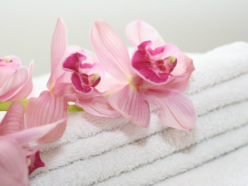 Badhanddoeken met orchideeën stock foto