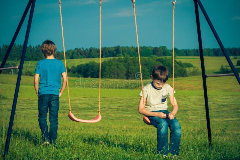 Badine des difficultés de relations L'enfant tombe avec un ami images stock