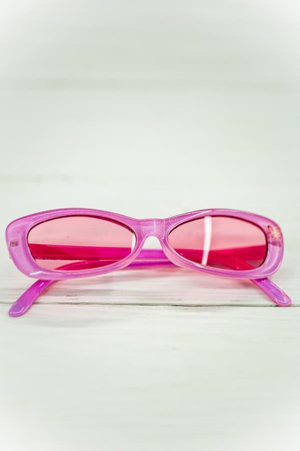 badine des lunettes de soleil sur le fond blanc photos stock