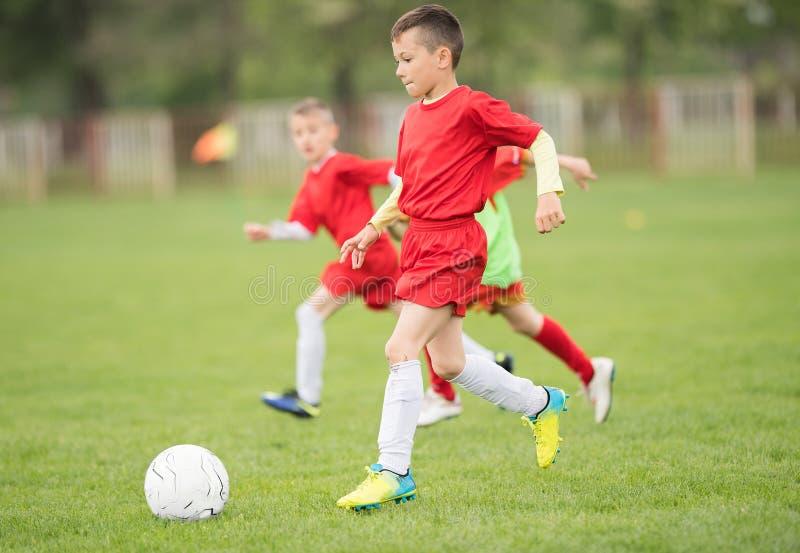 Badine le football du football - les joueurs d'enfants sont assortis sur le terrain de football photo libre de droits