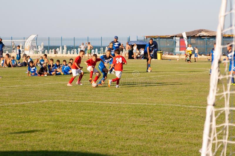Badine le football du football - les joueurs d'enfants en bas ?ge sont assortis sur le terrain de football photos stock