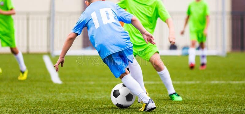 Badine le match de football Garçons donnant un coup de pied la boule du football sur le champ de sports photo libre de droits