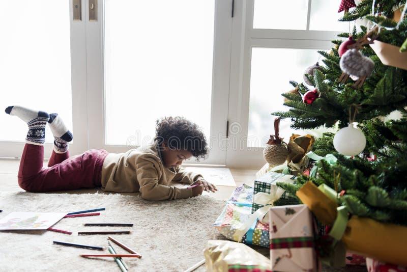 Badinez apprécier livre de coloriage dans la pièce décorée par Noël photos libres de droits