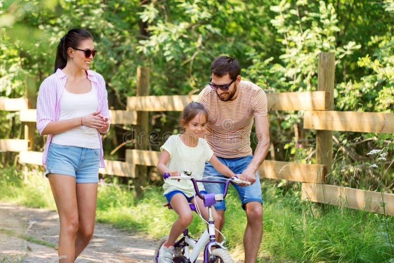 Badinez avec des brevets apprenant à monter la bicyclette en parc photographie stock