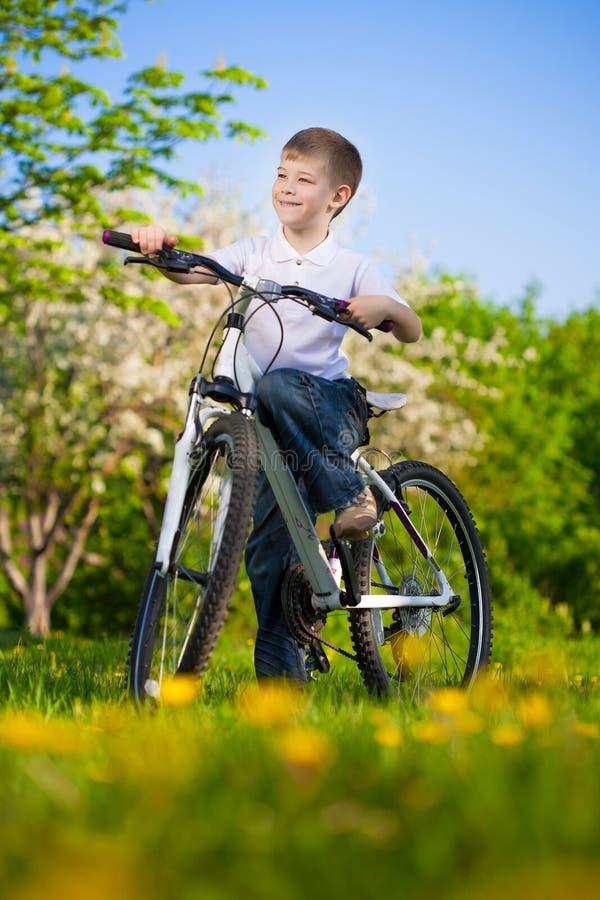Badinez en parc vert sur un vélo photo stock