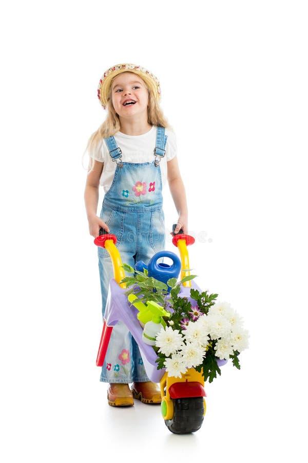 Badinez la fille avec les fleurs et l'équipement de jardinage mis en pot images libres de droits