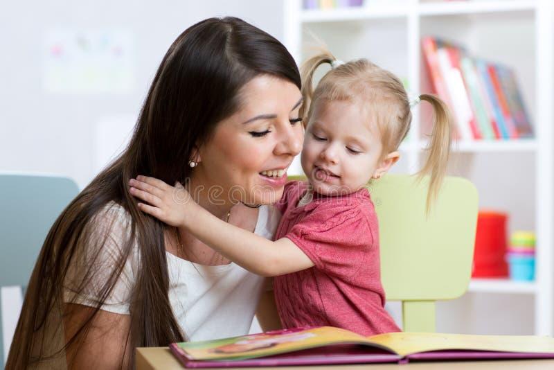 Badinez la fille et la mère a lu un livre ensemble à l'intérieur photos stock