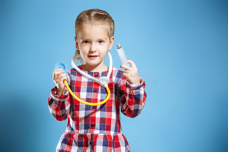 Badinez la fille jouant le docteur avec la seringue et le stéthoscope sur un fond bleu images stock