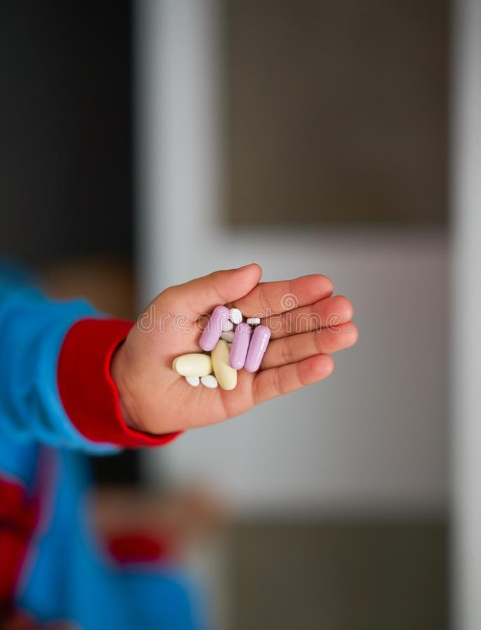 Badinez la main tenant des pilules et la capsule pour que mangent traitent les soins de santé vi photographie stock