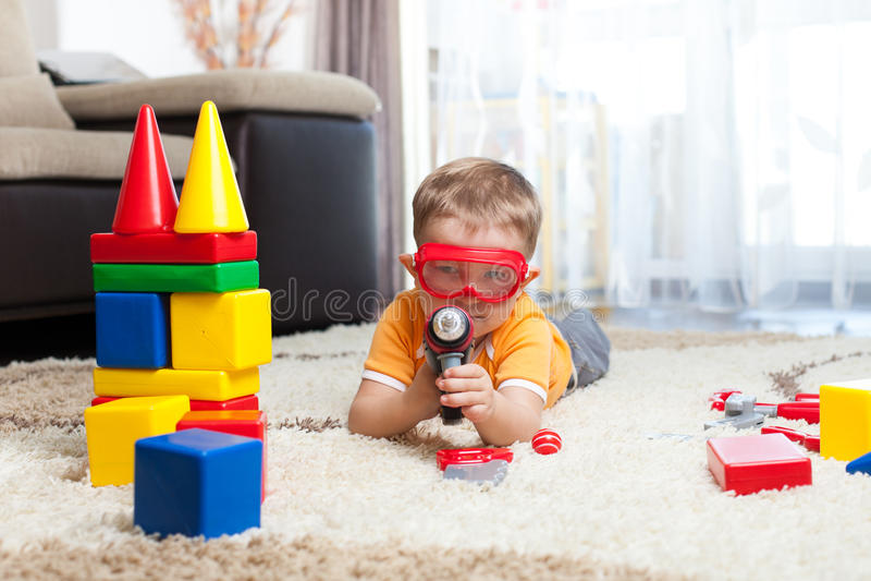 Badinez le garçon jouant avec les blocs constitutifs et s'imaginant un héros images libres de droits