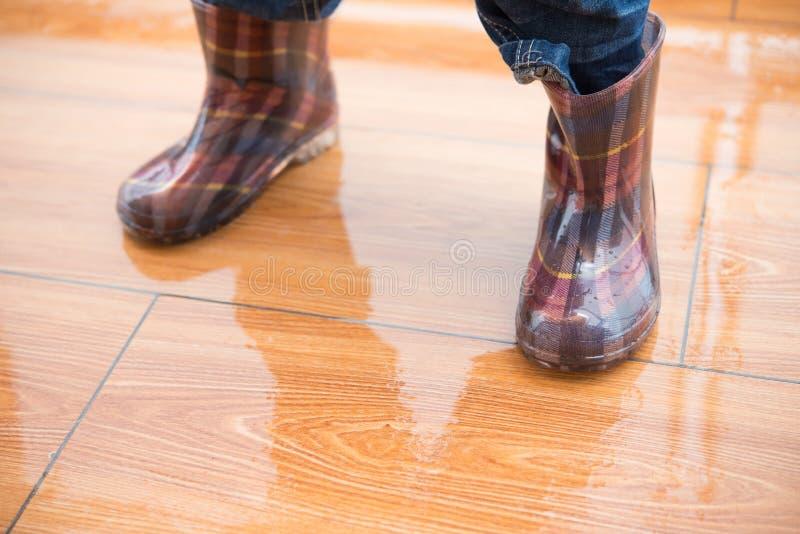 Badinez les bottes de caoutchouc imperméables de port se tenant sur le plancher humide photos libres de droits