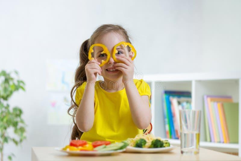Badinez manger de la nourriture saine dans le jardin d'enfants ou la maison images stock