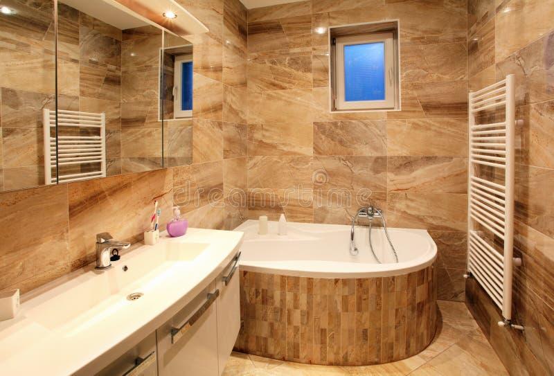 Badkamers in luxehuis met bad en meubilair stock afbeeldingen